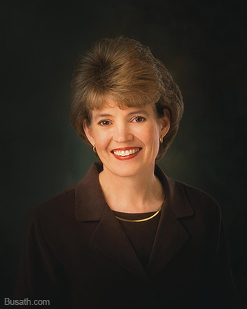 A photograph of Susan Winder Tanner against a dark gray background, wearing a dark brown blazer and gold necklace.