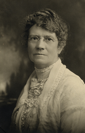 A black-and-white photograph of Ruth May Fox wearing a white dress and lace collar.