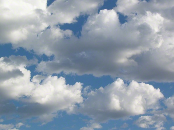 Big, white, fluffy clouds sit below a blue sky.