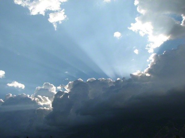 Sun rays extend upward above a group of dark gray clouds into the blue sky.
