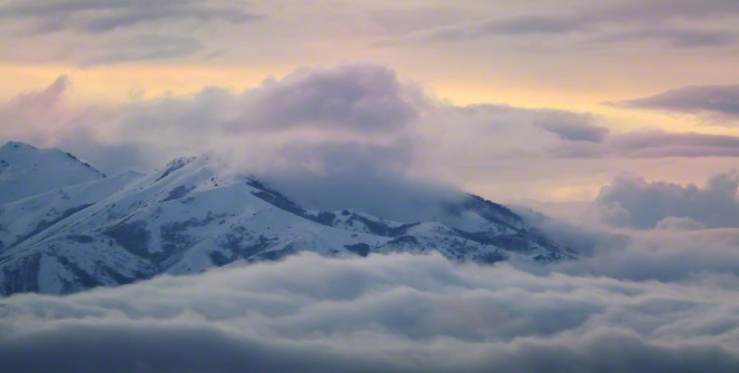 A snow-covered mountain pokes up above a layer of soft clouds as the sun sets, with the sky colored soft pink, purple, and yellow from the sunset.