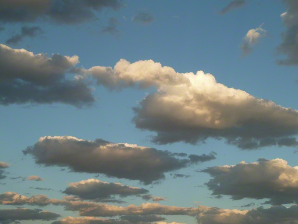 Small groups of white and gray clouds are spread out over a big blue sky.