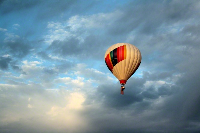 A white hot air balloon, decorated in colored stripes, is seen flying through white and gray clouds, with blue sky poking through the clouds.