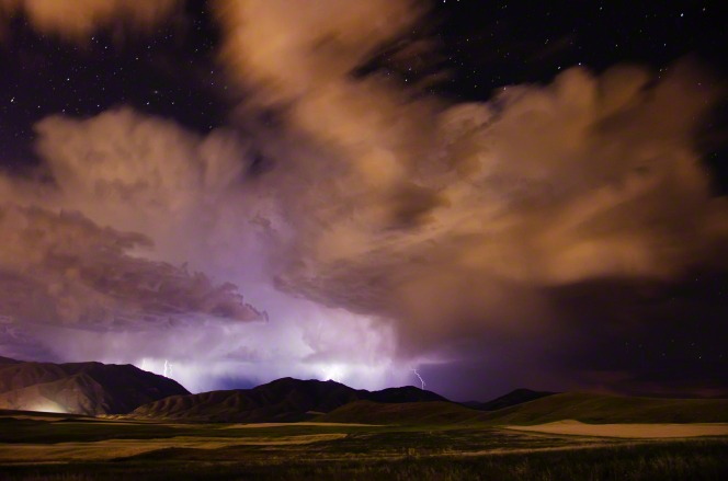 Lightning coming out of big storm clouds at night, striking down over mountains. Stars are seen overhead, above the storm.