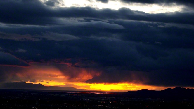 Dark storm clouds gather over a valley while the sun sets in the distance, reflecting deep orange and yellow sunlight.