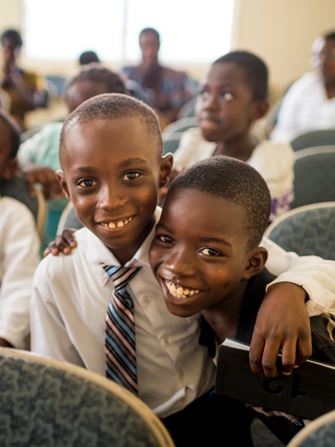 Two Primary-age boys in Ghana, smiling, with their arms wrapped around each other.