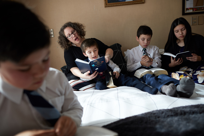 A mom sitting on a bed with her three sons and one daughter, reading the scriptures together.