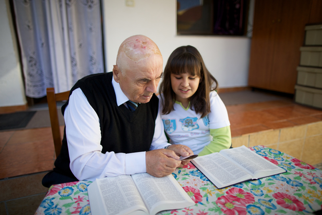 A grandfather sits with his granddaughter at the kitchen table, each studying from the scriptures.