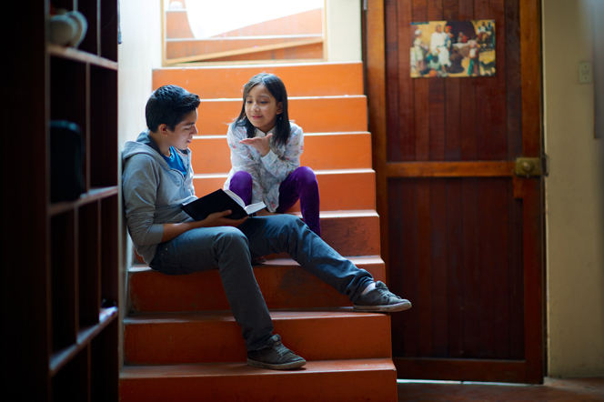 A brother and sister sitting on the stairs, reading from the scriptures.