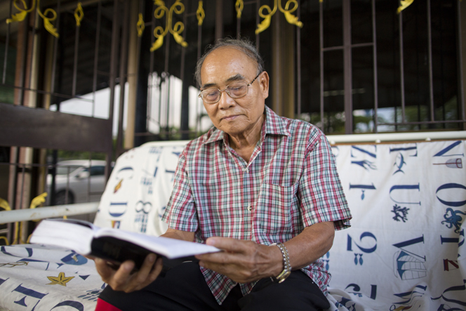 A man wearing glasses sits on his outdoor couch, reading the scriptures.