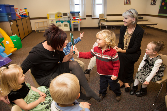 A photo of nursery-age children singing and interacting.