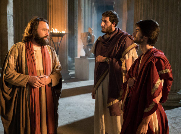 Peter with his hands clasped in front of him, teaching two men.