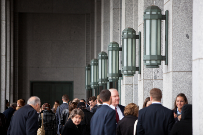 A group of people in Sunday dress outside of the doors of the Conference Center, with the building's large light fixtures seen overhead.
