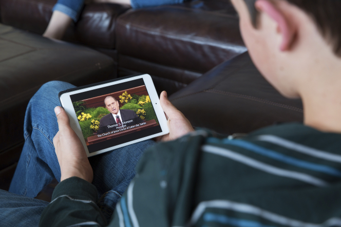A young man watching general conference on his tablet while sitting on a couch.