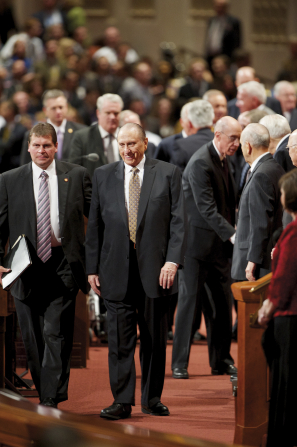 President Monson exiting the platform with his security guard, with General Authorities and other members nearby.