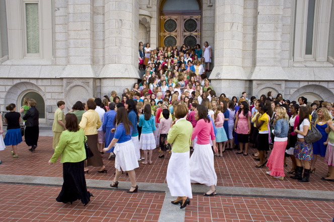 A large group of young women and their leaders standing on the stairs of the Salt Lake Temple, with some walking in the foreground.