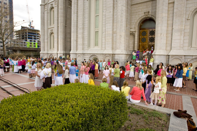 Groups of young women and their leaders stand together in dresses or skirts outside of the Salt Lake Temple.