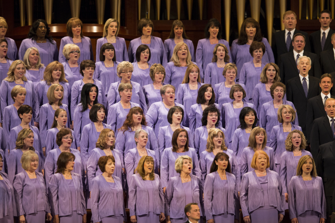 A group of women from the Mormon Tabernacle Choir wearing purple dresses and singing.