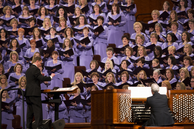 Ryan Murphy in a black suit stands in front of the women of the Mormon Tabernacle Choir to conduct a song.