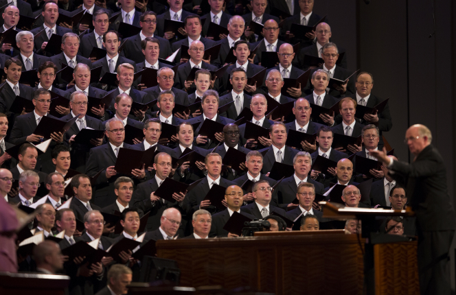 Rows of men from the Mormon Tabernacle Choir wearing dark suits and singing while Mack Wilberg conducts.