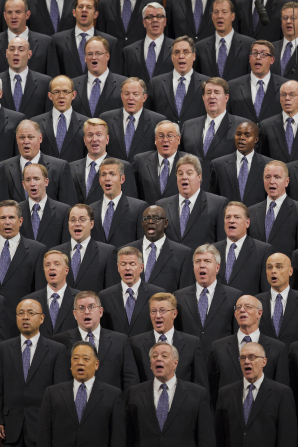 A group of men wearing black suits and purple ties, singing together at a session of the April 2013 general conference.