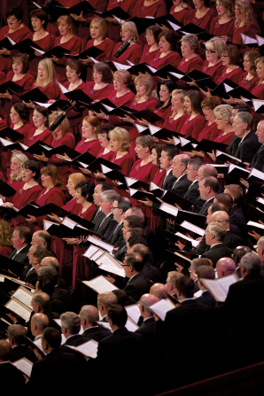 Rows of women in red dresses and men in black suits singing together in the Conference Center.
