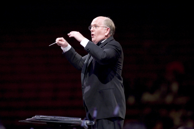 Mack Wilberg in a black suit, standing behind a music stand and conducting the choir with both arms.