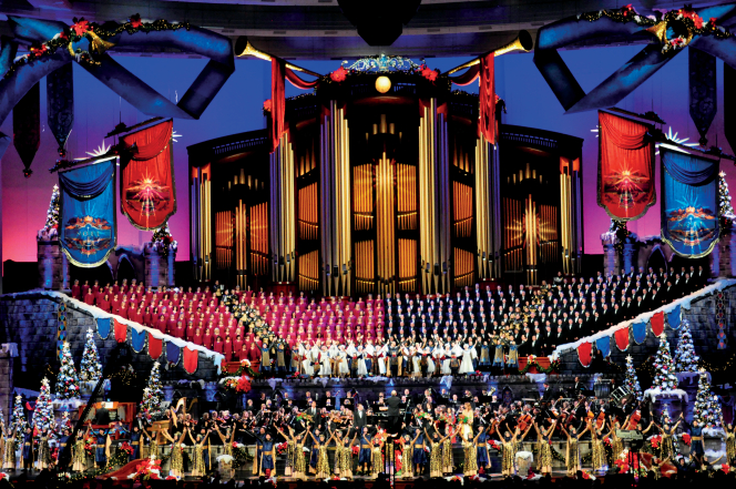 The Mormon Tabernacle Choir and Orchestra at Temple Square onstage at the Conference Center, which is decorated with Christmas trees and banners.