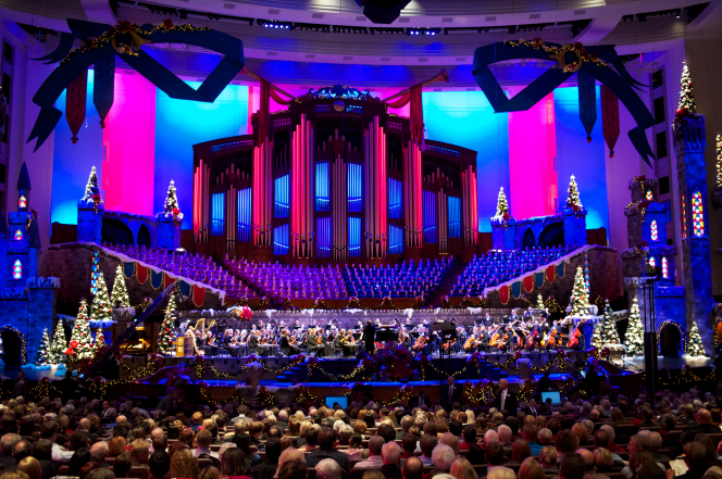 An audience watching the Mormon Tabernacle Choir, orchestra, and dancers perform with a purple and blue backdrop at the Christmas concert in 2011.