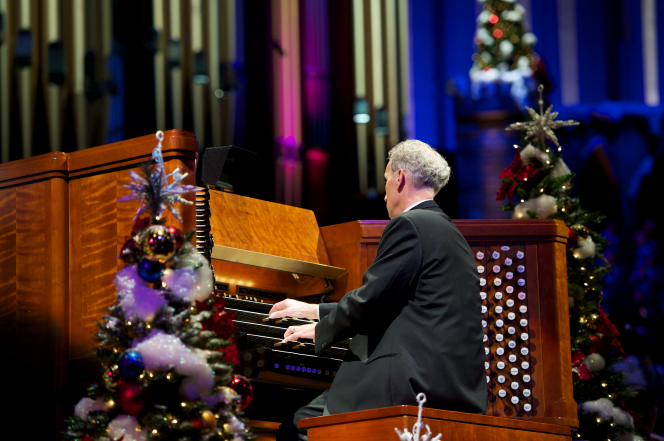 A man in a black suit playing an organ next to decorated Christmas trees in the 2011 Christmas concert in the Conference Center.