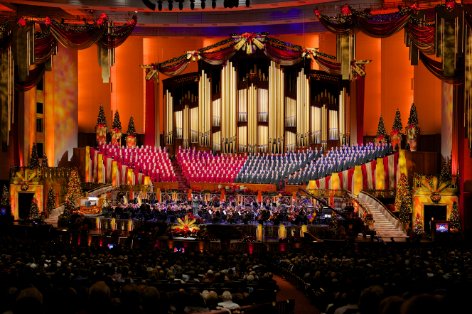 A view of the audience watching the Mormon Tabernacle Choir and orchestra, who are bordered by red curtains at the 2012 Christmas concert.