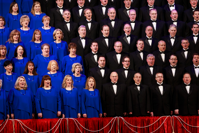 Rows of women in blue dresses and men in black tuxedos singing in the Mormon Tabernacle Choir behind a red partition.