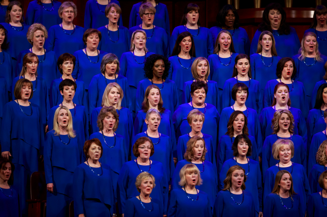 A section of women from the Mormon Tabernacle Choir wearing blue dresses and necklaces, singing in the Conference Center.