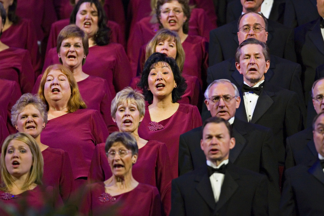 Women in maroon dresses and men in white shirts, black suits, and black bow ties, singing in the Mormon Tabernacle Choir.