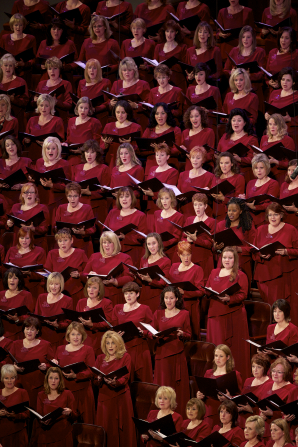 Rows of women in bright red dresses hold their music in folders and sing in the Conference Center with the rest of the Mormon Tabernacle Choir.