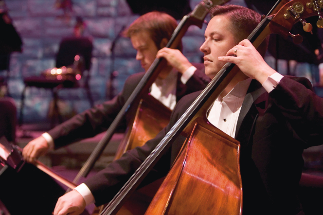 Two men in black tuxedos play double basses at a concert, with Christmas decorations faintly seen in the background.