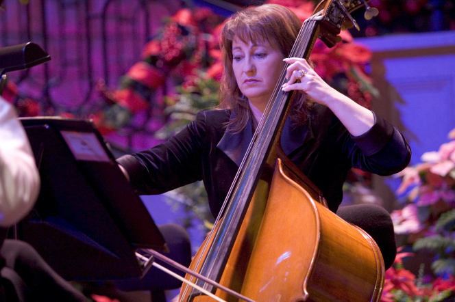 A woman in a black jacket plays the double bass, with Christmas decorations seen in the background.