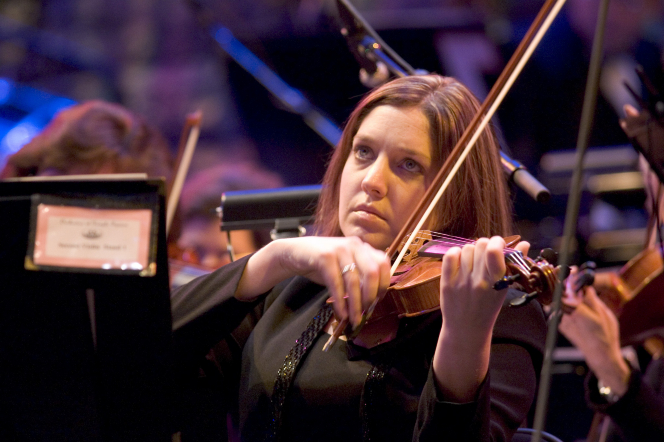 A female violinist sits in a chair and plays the violin while looking up at the conductor.