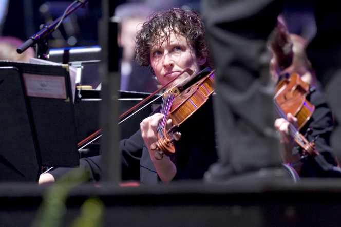 A violist plays her instrument while looking up at the conductor, whose legs are seen in the foreground.
