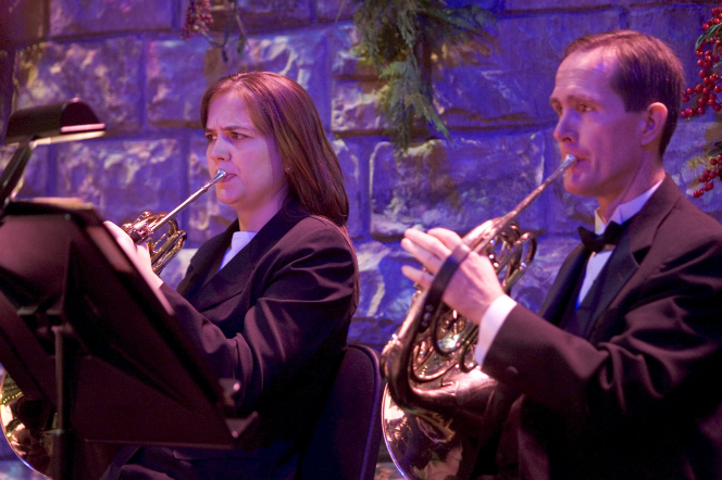 A man and a woman in black jackets playing French horns, with Christmas decorations seen in the background.