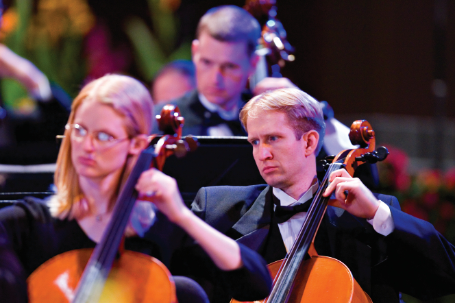 A man in a black tuxedo plays a cello onstage in the Conference Center, with one cellist in front of him and another behind him.