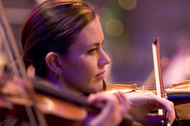 A woman with a ponytail plays the violin, with another violinist's hands in the foreground.