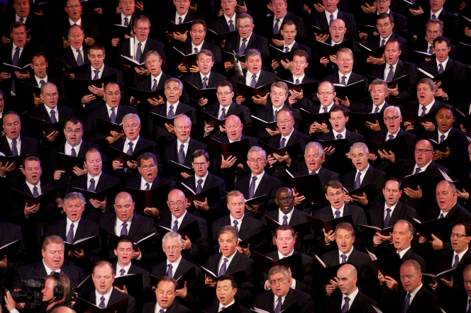 A section of the men from the Mormon Tabernacle Choir in black suits and purple ties, singing from the music they hold in their hands.