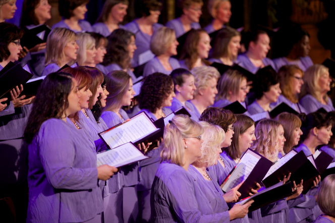 A section of women from the Mormon Tabernacle Choir seen from the side, holding their music in folders and singing.