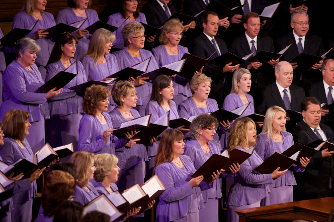 A section of the women in the Mormon Tabernacle Choir wearing purple dresses and sweaters and singing from music they hold in their hands.