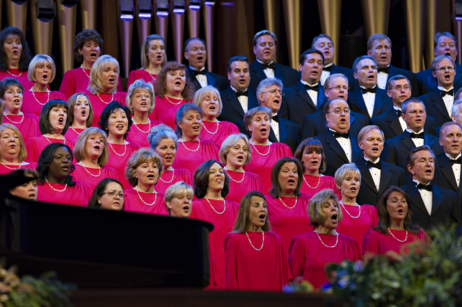 The Mormon Tabernacle Choir, with the women in red dresses and the men in black suits, singing in the Pioneer Day Commemoration Concert in July 2008.