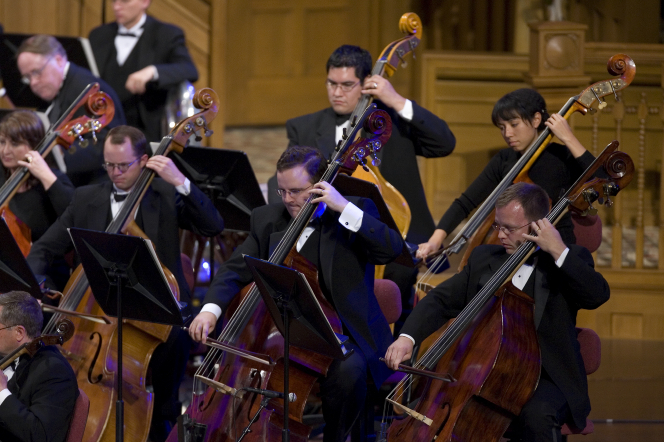 Men in black suits and women in black dresses looking down at sheet music while playing in the orchestra in the Conference Center.