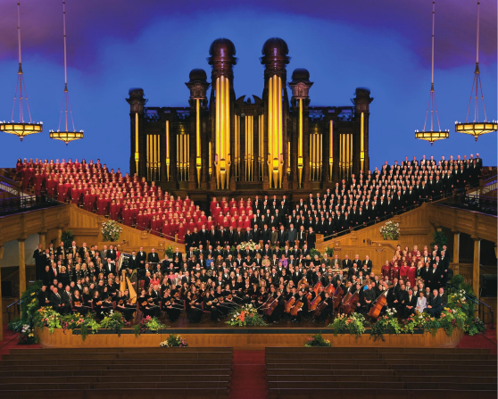 The Mormon Tabernacle Choir with the women in red dresses and the men in black suits, with the orchestra in black in the foreground.