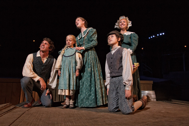 Three actresses standing in green dresses and two actors kneeling on a lighted stage in the British Pageant.