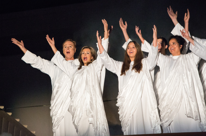 Adult male and female angels wearing white and singing with raised arms in the Arizona Christmas pageant.